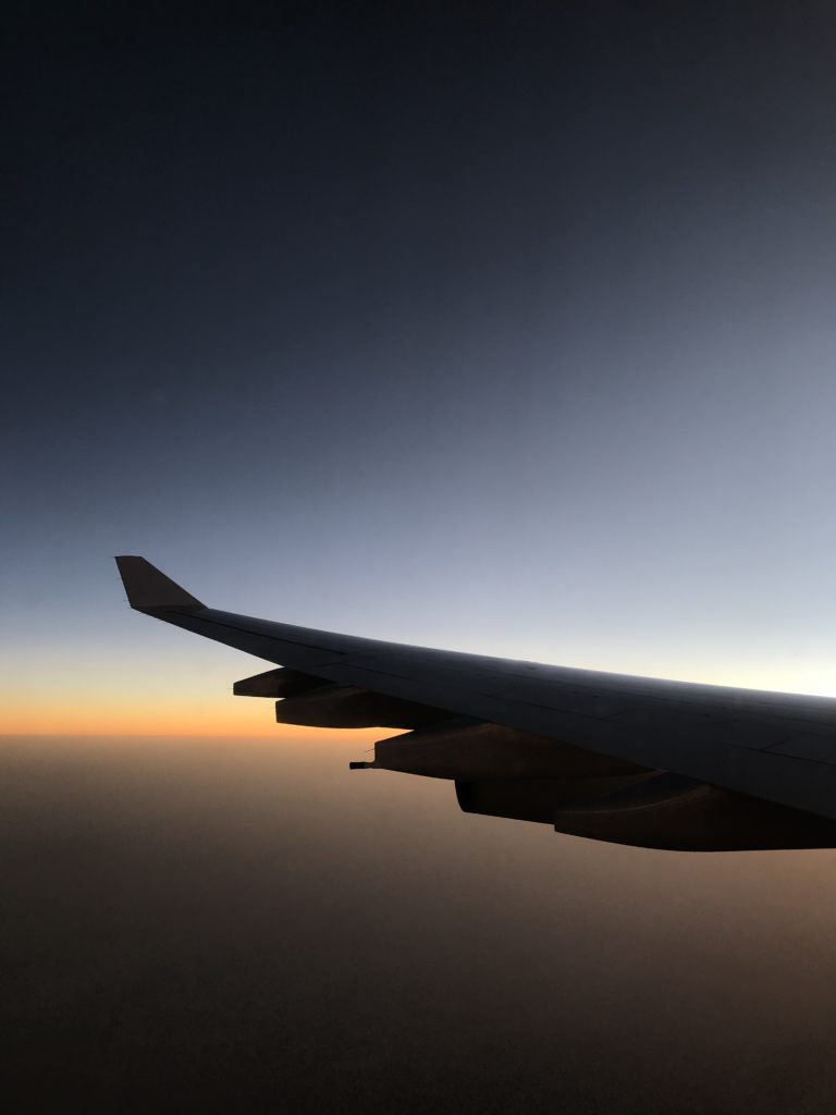 The view from the airplane window to the left airplane wing with sunrise in the background.