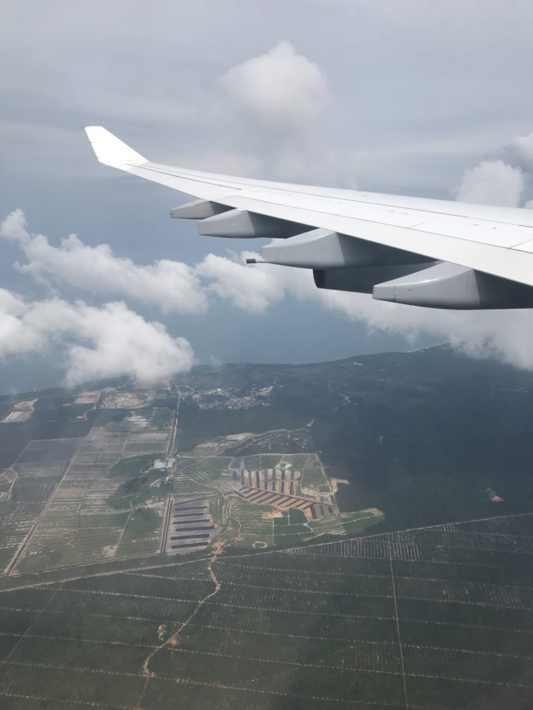 The view from my airplane window to the left airplane wing with fields in Malaysia in the background.