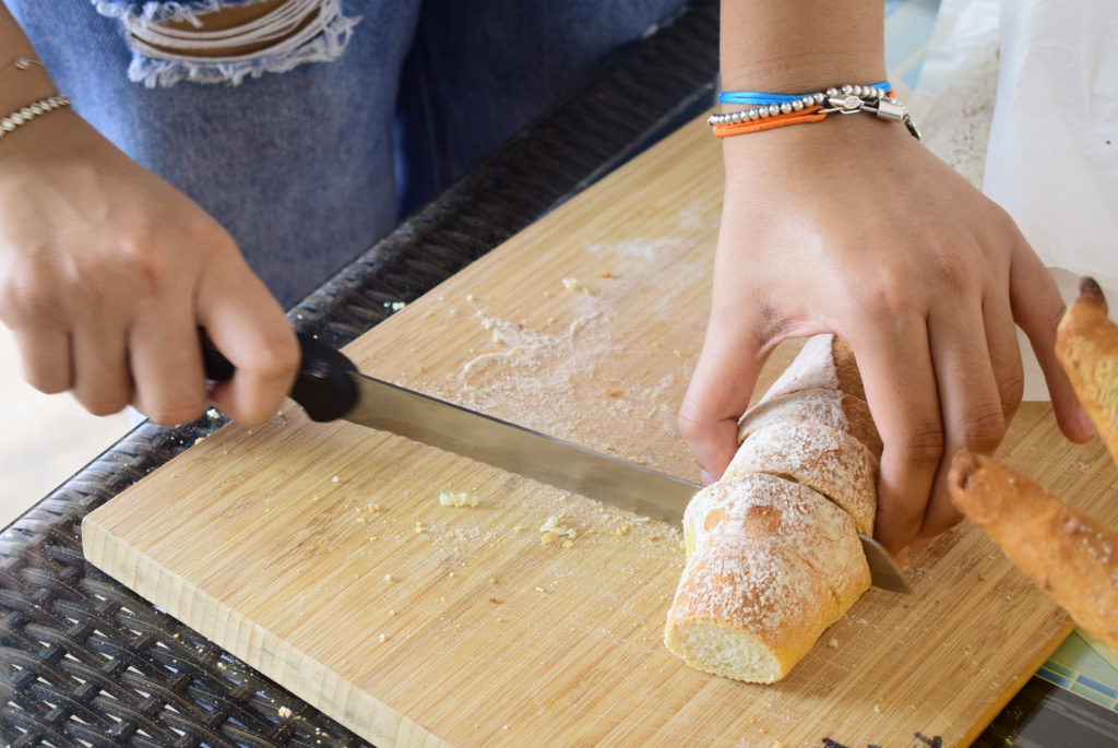Two hands cutting baguette.