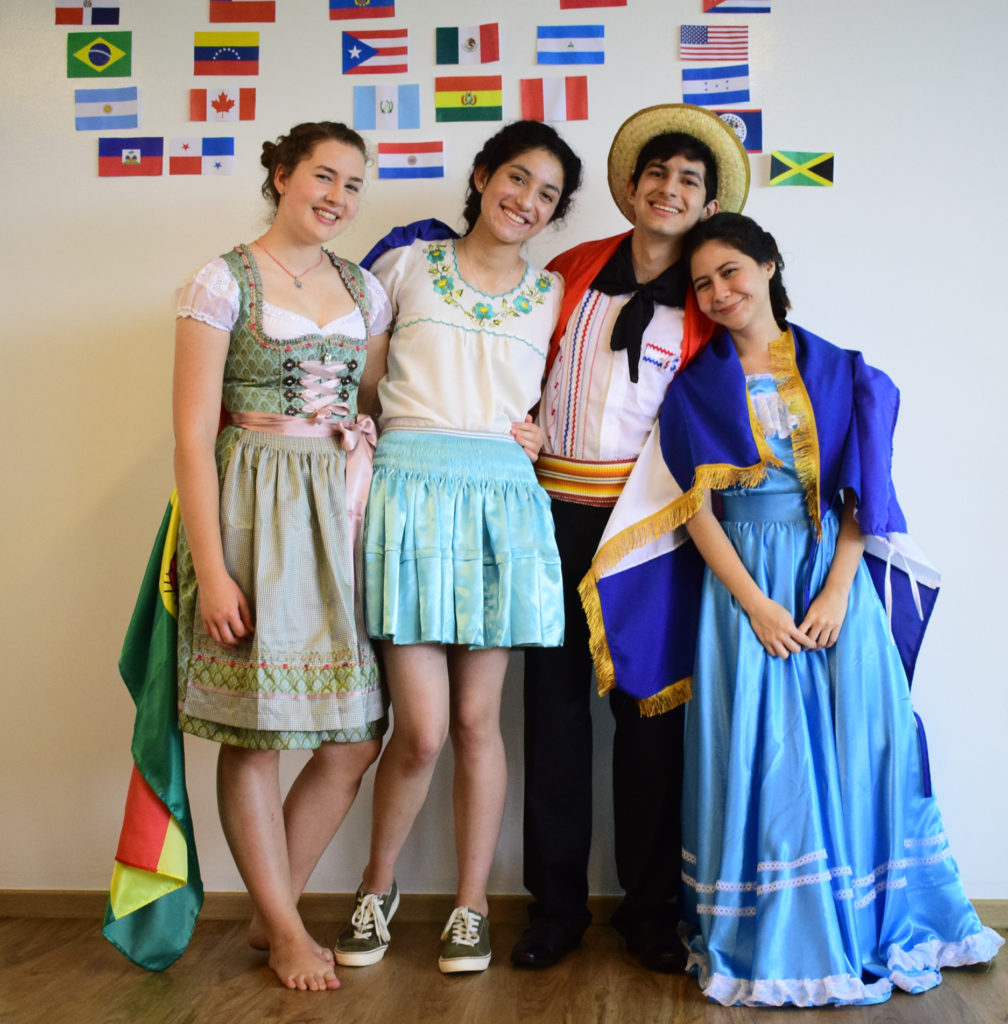 Milena together with three of her friends from Bolivia, Paraguay and El Salvador, all smiling in their costumes.
